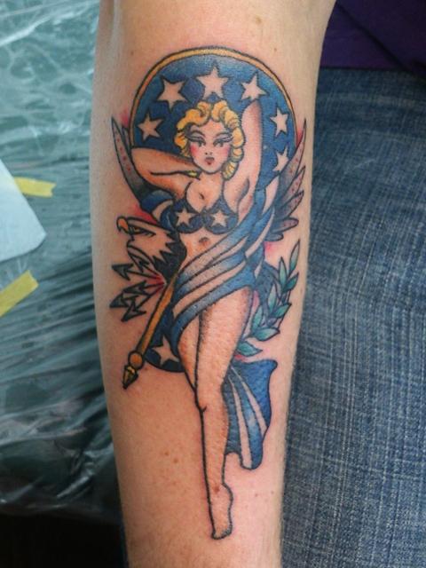腕にピンナップガールとイーグルのタトゥー