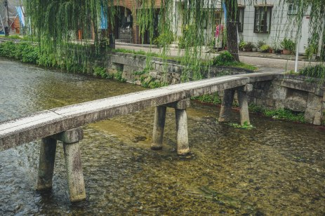One of many bridges spanning the shallow river along a street in Kyoto.