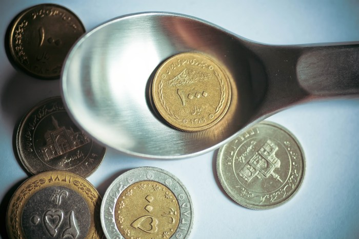 One thousand Iranian rials on a dinner spoon