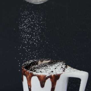 Espolvoreando azúcar sobre un mug de nutella.