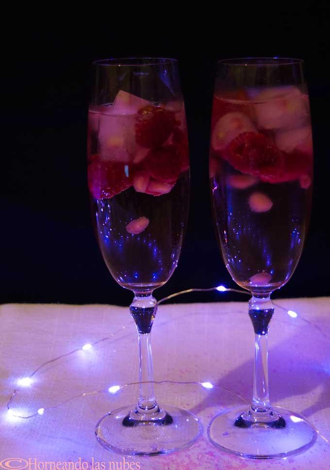 Copas de champagne con cubitos de granada y frambuesas congeladas.