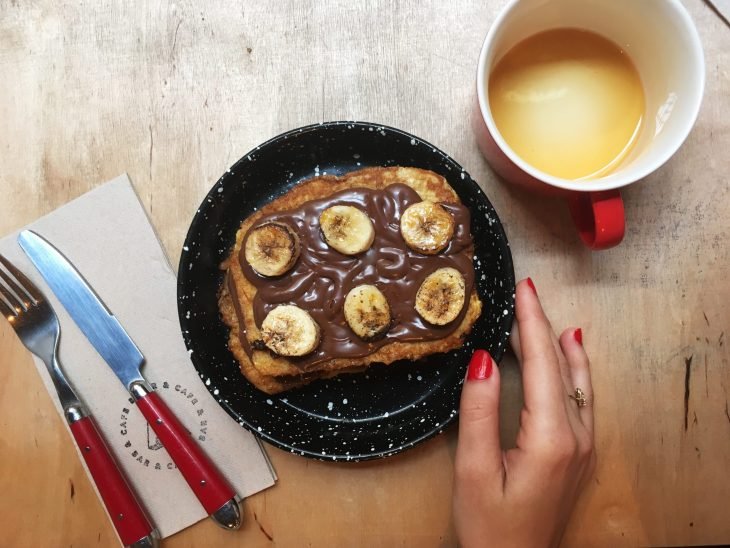 French toast sandwich filled with nutella and banana slices on top