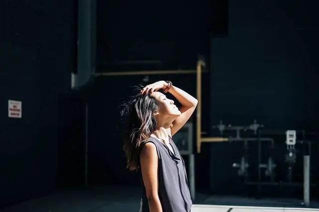 Mujer acariciando su cabello y mirando el sol