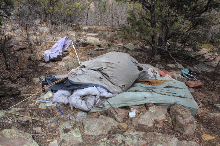 A decrepit tent, mattress and trash pile on top of it--on City-owned open space in Horse Gulch.