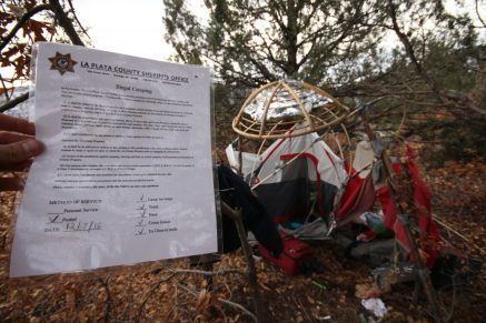 A tag left at an abandoned homeless camp by the La Plata County Sheriff's Office outlines violations.