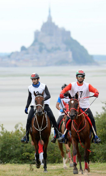 Winners HE Sheikh Hamdan bin Mohammed Al Maktoum (left) and Nikos, with HE Sheikh Rashid Dalmook Al Maktoum and Yamamah pictured in front of the iconic Mont Saint-Michel at the endurance test event for WEG 2014 in Normandy, France