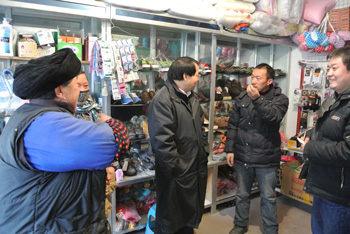 Jack Liu, left, and Jindong Zhang talk to a farmer in the Wolong Nature Reserve about the impact livestock can have on panda habitat.