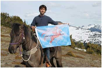Filippe Masetti's horseback journey covered 16,000km.  He is pictured holding the flag of the Long Riders' Guild.