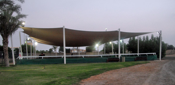 A giant sail helps keep both horse and rider cool on one of the arenas at the Emirates Equestrian Centre.
