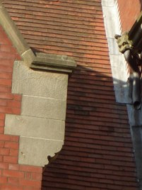 A gargoyle with guttering in his mouth