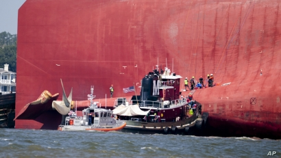 Rescuers work near the stern of the vessel Golden Ray as it lays on its side near the Moran tug boat Dorothy Moran, Monday, Sept. 9, 2019, in Jekyll Island, Ga. The Golden Ray cargo ship is capsized near a port on the Georgia coast. (AP Photo…