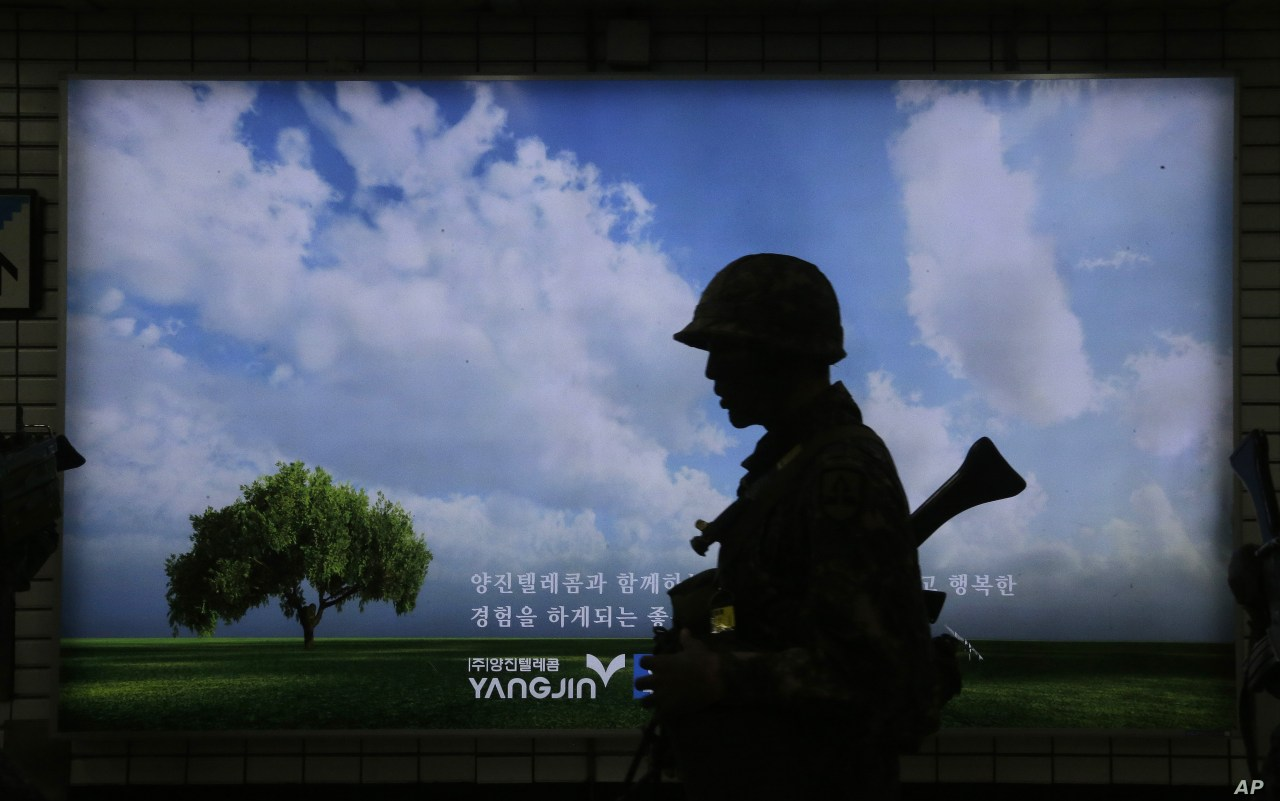 A South Korean army soldier passes by an advertising board during an anti-terror drill as part of Ulchi Freedom Guardian exercise, at Sadang Subway Station in Seoul, South Korea, Aug. 19, 2015.