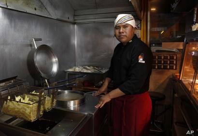 Rolando Condori, chef at his own fast food restaurant, poses for a portrait in his restaurant's kitchen in El Alto, Bolivia, Sept. 14, 2019.