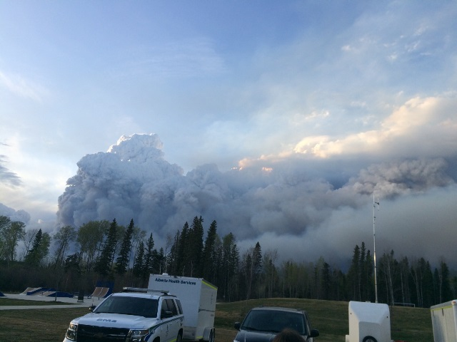 Wildfire smoke billows up behind an AHS EMS unit. EMS crews remained a constant presence throughout the evacuation, to provide support as needed.
