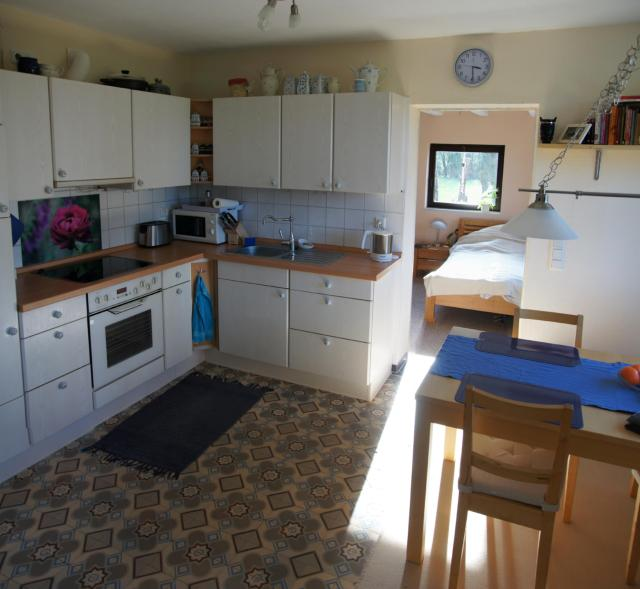 The new kitchen with the old floor tiles and the new bedroom