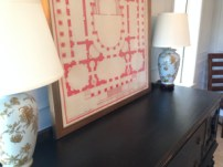 The bold red of the architectural print is a nice juxtaposition to the delicate porcelain lamps.