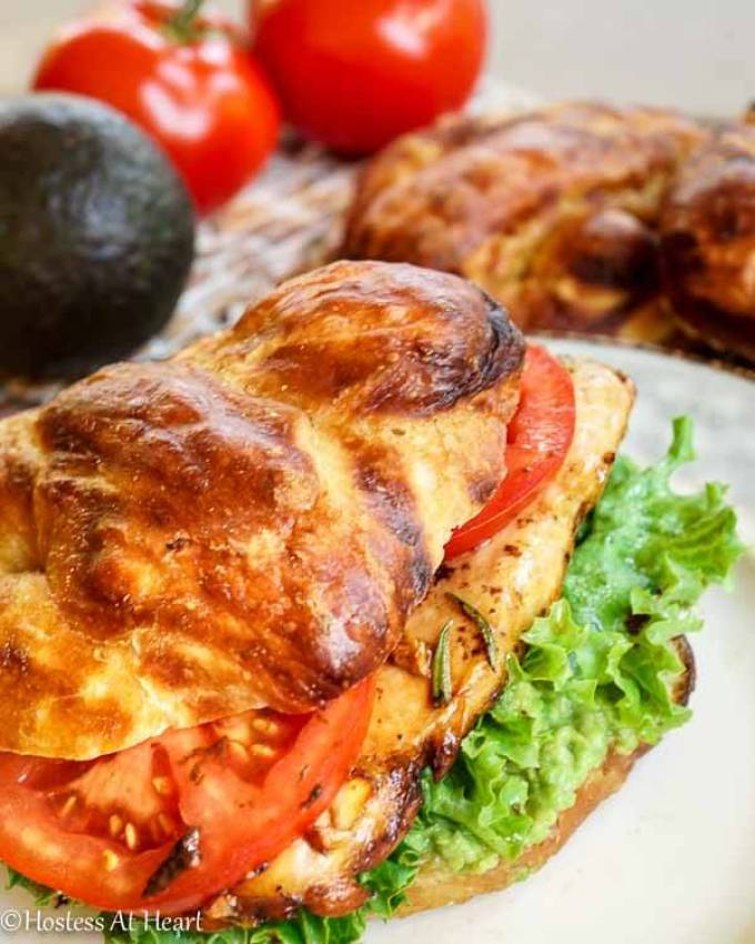 This Balsamic Chicken Sandwich combines that soft in the center and nice brown briny exterior that you look for in a pretzel bun with a sweet balsamic glaze, avocado, and tomato, all piled on a thick grilled chicken breast - Hostess At Heart