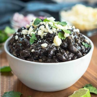 Side view of a bowl of black beans garnished with cheese and cilantro