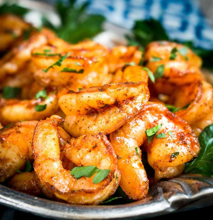 Baked Blackened Shrimp piled on a plate and garnished with fresh parsley