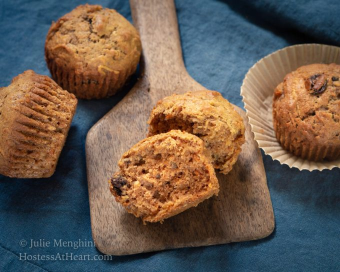 Horizontal view of 3 whole muffins and one split muffin.