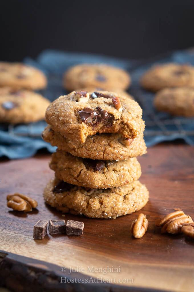 Stack of 4 cookies with a bite out of the top one.