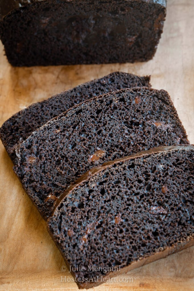 3 slices on dark chocolate banana bread on a wooden cutting board