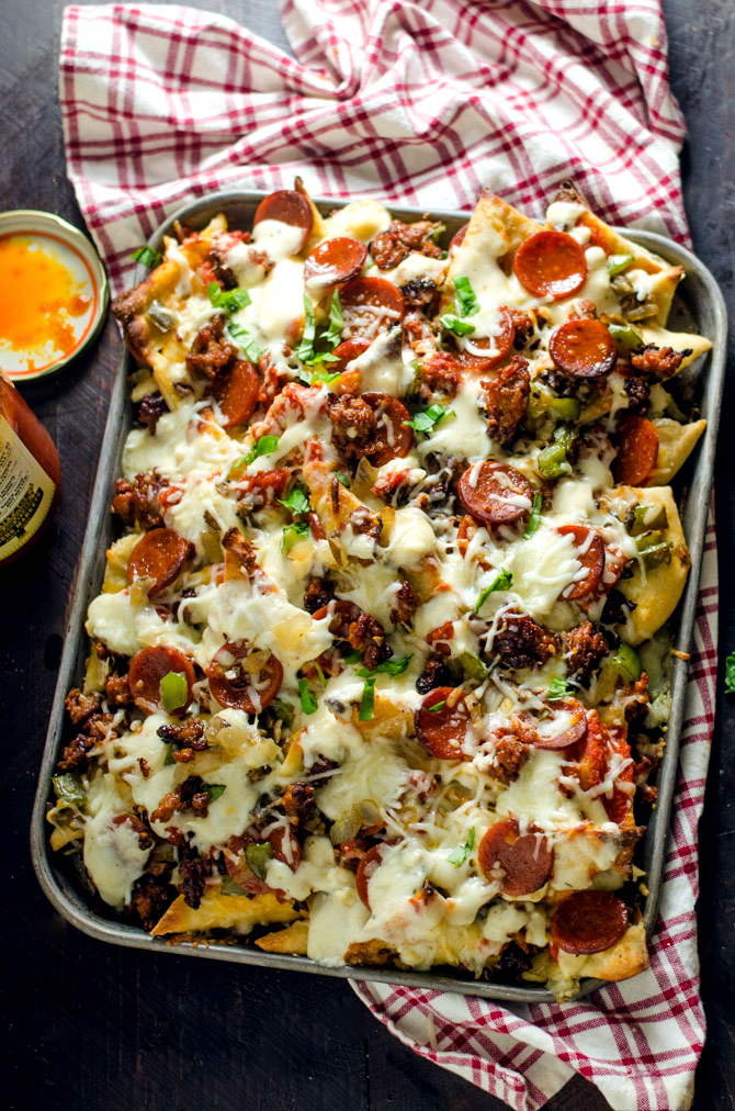 Loaded Pizza Nachos with Creamy Garlic White Sauce. All of your favorite pizza toppings on easy-to-make pizza crust chips. This is the ultimate appetizer. | hostthetoast.com