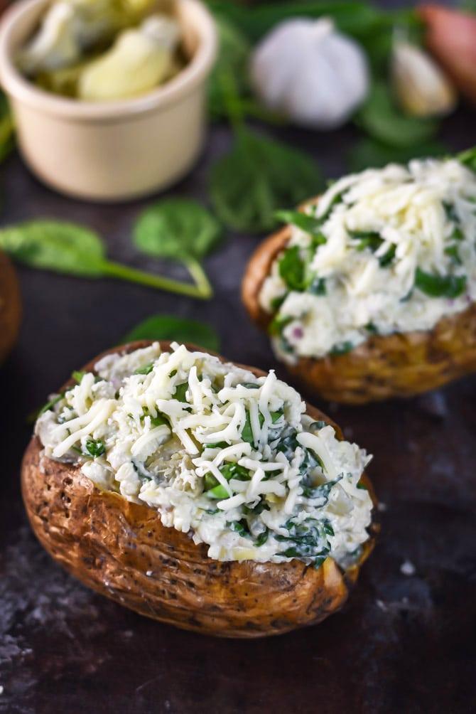Spinach and Artichoke Dip Baked Potatoes. Hearty baked potatoes with a creamy, cheesy spinach and artichoke dip filling. | hostthetoast.com