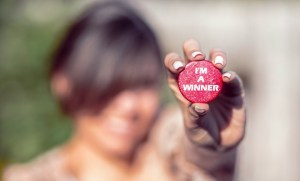 Woman-Holding-Red-button-Saying-Im-A-Winner