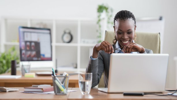woman-CEO-smiling-with-computer-at-desk-measuring-ROI-hot-dog-marketing