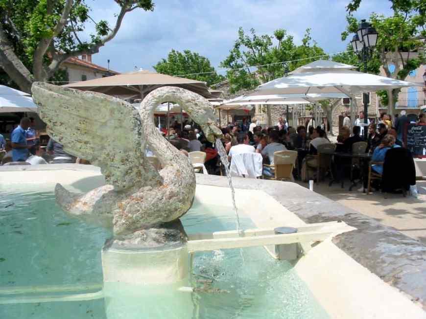 Fontaine des 4 Saisons et restaurant sur la place du village.