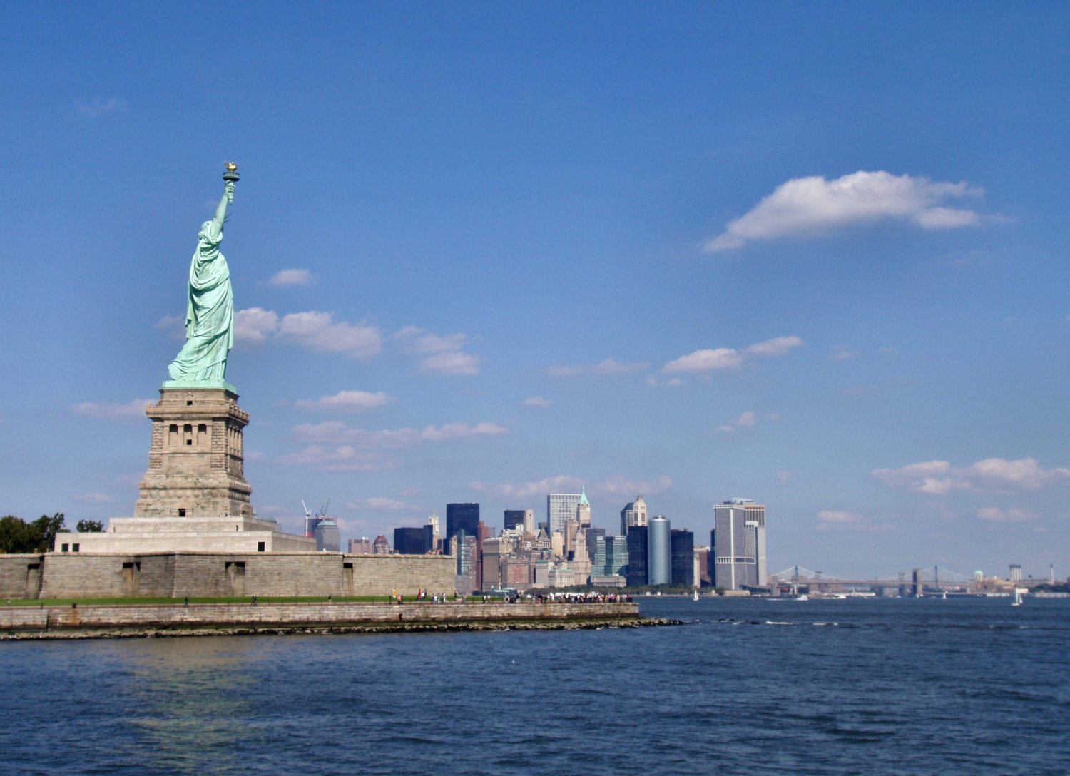 This picture shows the statue of Liberty view from Staten Island, the sky is bleu and we can see tourists