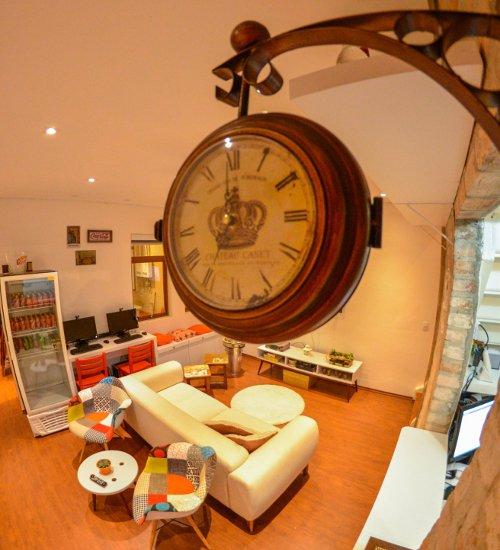 Sala de estar do hotel didshostel com um relógio antigo pendurado