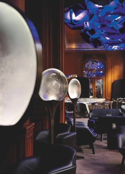 Au bar, allégories et jeux de matières : le bar emprisonne les vapeurs d'alcools, le mobilier offre des lignes raffinées avec surpiqûres sellier sur cuir, les disques en verre sur pied diffusent une douce lumière.