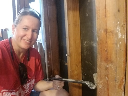 J crouched and removing nails from a house frame stud with a crowbar