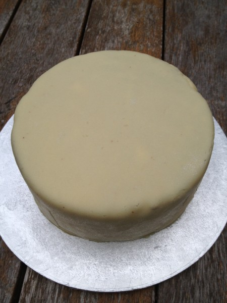 Covering the cake in marzipan stops the white icing staining brown