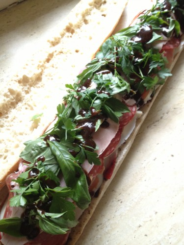 The ham, prosciutto and salami layers have been added, the herbs have been scattered and the dressing drizzled