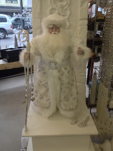 A large Santa all in white with silver Cinderella shoes next to him.
