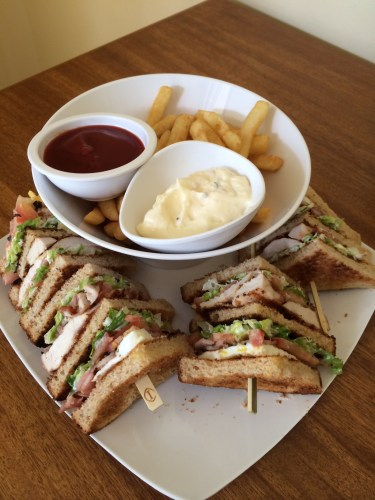 Club sandwich with fries with sauce and aioli