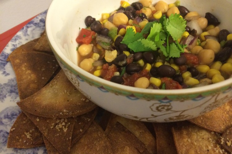 Bowl of corn and black bean salsa with baked tortilla chips on a plate.