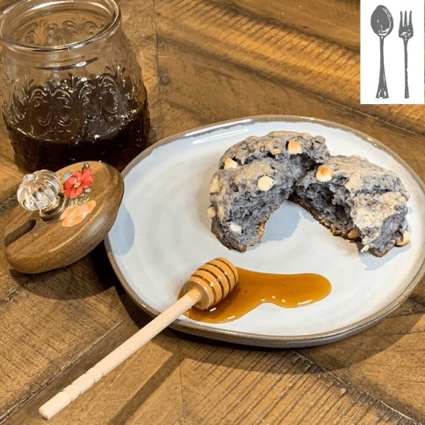 A blackberry scone is split in half and sits on a plate with pooling honey. The honey jar is open behind it.