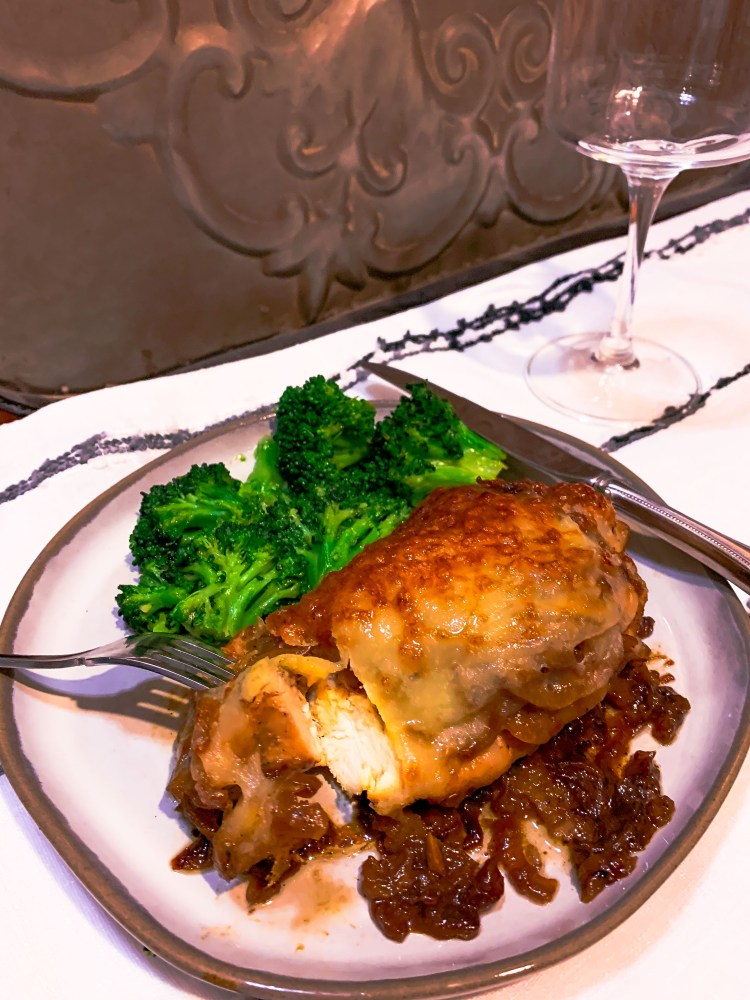 French Onion Chicken breast on a plate with green broccoli.