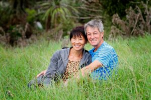 Martin and Rebecca in the grass at Tawharanui Beach regional park, Auckland new Zealand