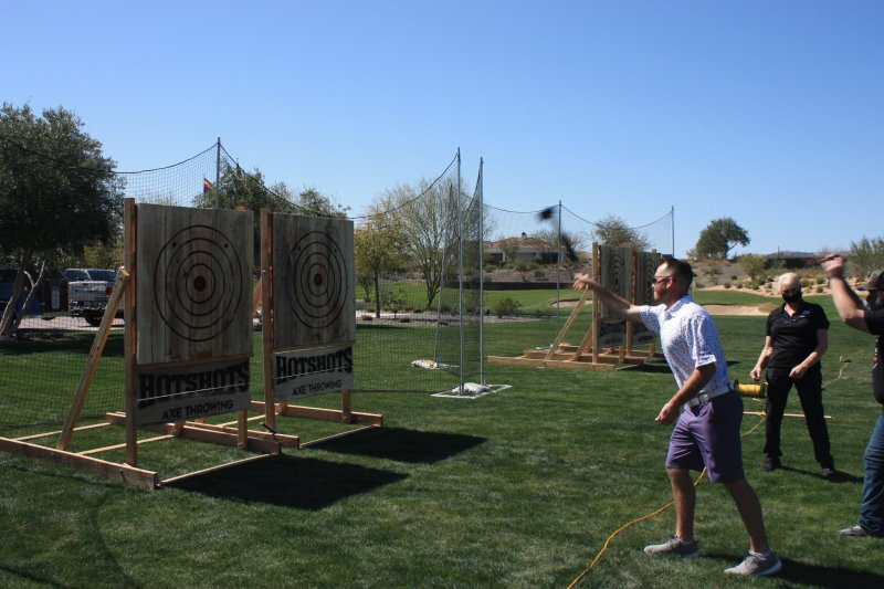 Mobile Axe Throwing - Man throwing an axe at a target in a green golf field.