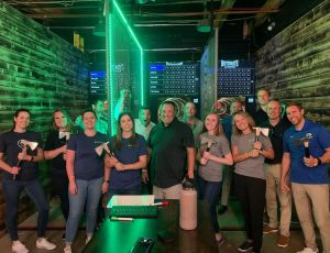 A group of people posing in front of the Hotshots Axe Throwing targets.