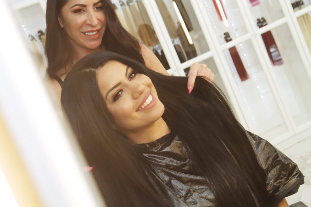 Hair Stylist Showing Client How To Maintain Beaded Weft Hair Extensions in Las Vegas at Hottie Hair Salon & Extensions Hair Store Las Vegas