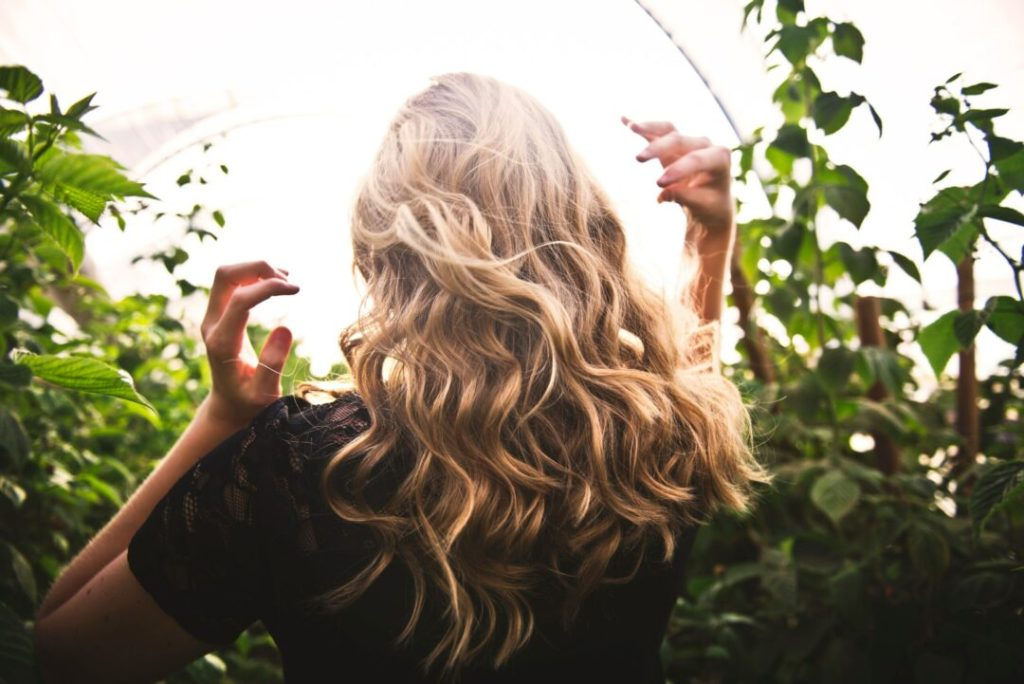 blonde haired woman standing between green plants with curled hair extensions