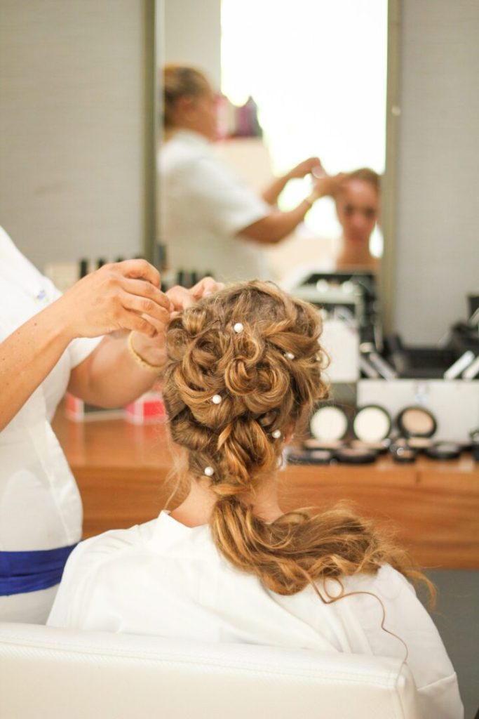 bride getting her hair extensions done in preparation for wedding day