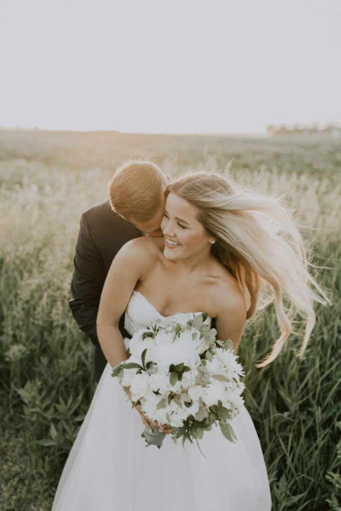 bride hugged by groom with long hair extensions flowing in the wind