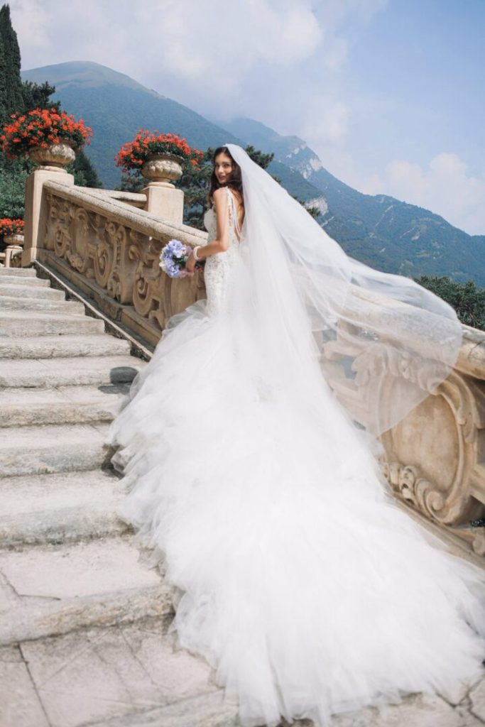 bride wearing white dress with long train and long hair extensions complimented with a long white wedding veil